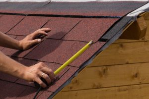 roofs in omaha measuring with a tape measure on shingles